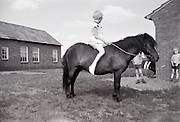 a young girl sitting on the back of a pony with other children looking on Holland