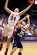 UD senior Justine Raterman (34) and Rhode Island freshman Megan Straumann (24) at the basket as the Rhode Island Rams play the University of Dayton Flyers at UD Arena in Dayton, Saturday, January 7, 2012.