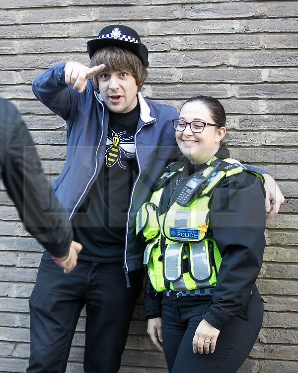 © Licensed to London News Pictures . 09/09/2017. Manchester , UK . A police officer lets a concert-goer wear her hat ahead of queuing to enter the venue . We Are Manchester reopening charity concert at the Manchester Arena with performances by Manchester artists including  Noel Gallagher , Courteeners , Blossoms and the poet Tony Walsh . The Arena has been closed since 22nd May 2017 , after Salman Abedi's terrorist attack at an Ariana Grande concert killed 22 and injured 250 . Money raised will go towards the victims of the bombing . Photo credit: Joel Goodman/LNP
