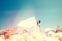 Woman in white on a mountain top.