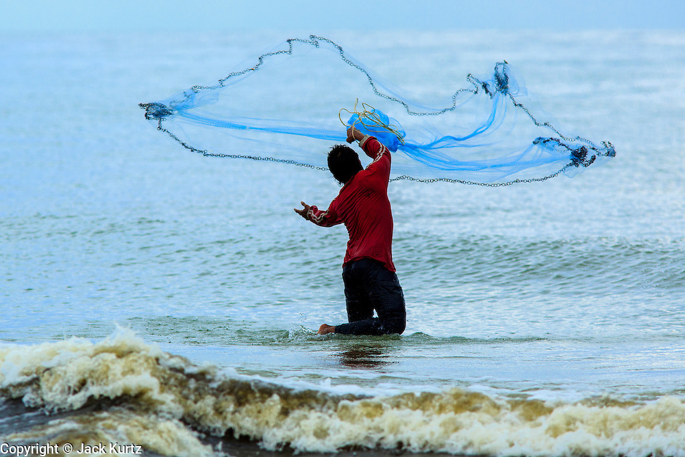04 NOVEMBER 2012 - KAO SENG, SONGKHLA, THAILAND:  Fisherman cast their nets from the surf in Kao Seng. The men had to fish from shore because the waves were too high for their small boats. Kao Seng is a traditional Muslim fishing village on the Gulf of Siam near the town of Songkhla, in the province of Songkhla. In general, their boats go about 4AM and come back in about 9AM. Sometimes the small boats are kept in port because of heavy seas or bad storms.    PHOTO BY JACK KURTZ