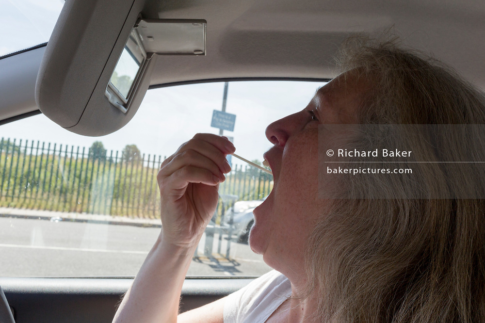 A middle-aged lady inserts a swab into her mouth to reach her tonsils from the driver's seat of her car during a self-administered Coronavirus (COVID-19) test in south London. There are four steps to the self-administered Covid-19 test (inserting a swab into the nose and throat) which the public works through in their car, windows up and all communications with army personnel via phone, in a south London leisure centre, on 2nd June 2020, in London, England. The kit provided consists of a booklet, plastic bag, swab, vial, bar codes and a sealable biohazard bag. The swab sample is taken from the back of the throat and nasal passage with the contents sealed and returned to soldiers through a narrow window. The whole process takes between 5-10mins with results available with 48hrs.