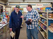 """25 FEBRUARY 2020 - BUTTERFIELD, MINNESOTA: DAVID LINSCHEID (left) and TIM HALL chat in the True Value Hardware Store in Butterfield, MN, a farming community of about 500 people 130 miles southwest of the Twin Cities. The town has been a """"food desert"""" for 10 years after its only grocery store closed in 2010. Linscheid's family opened the previous grocery store in town in 1905 and was forced to close it in 2010. Now Lincheid shops at the True Value. Barb Mathistad Warner and Mark Warner purchased the True Value store in Butterfield in December, 2018 and started selling groceries in the store in May, 2019. For residents of Butterfield going to a grocery store meant driving 10 miles to St. James, MN, or 20 miles to Windom, MN, the two nearest communities with grocery stores. The USDA defines rural food deserts as having at least 500 people in a census tract living 10 miles from a large grocery store or supermarket. There is a convenience store in Butterfield, but it sells mostly heavily processed, unhealthy snack foods that are high in fat, sugar, and salt.    PHOTO BY JACK KURTZ"""
