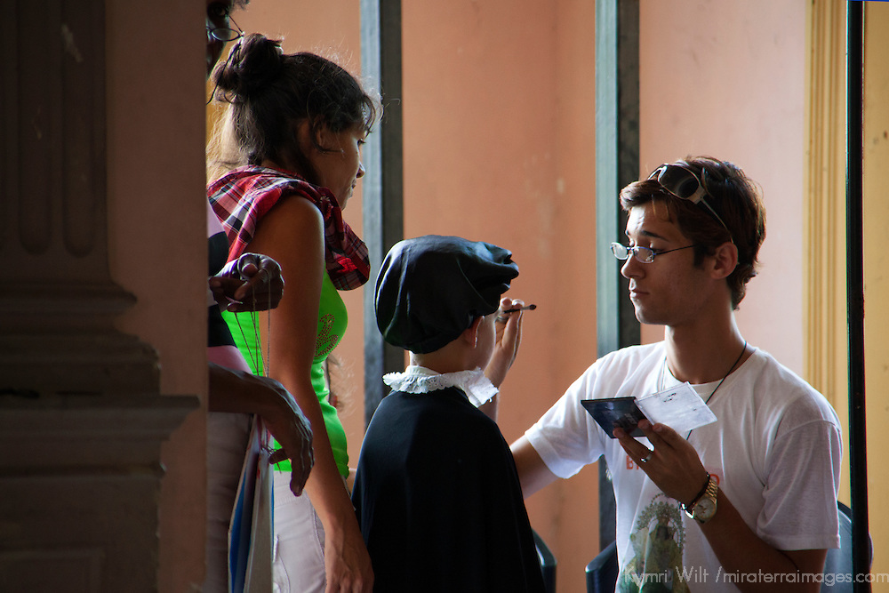 Central America, Cuba, Santa Clara. Make Up Artist prepares young actor for performance.