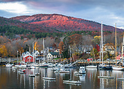 A beautiful glow lights the peak of Mount Megunticook over Camden Harbor. Several sailboats and lobster boats still sit in the water, late in the season, and the last few leaves hang on the trees.