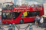 MONACO, MONACO - JUNE 17, 2015: Unidentified people enjoy sightseeing tour on the red Monaco city tour bus in Monaco.