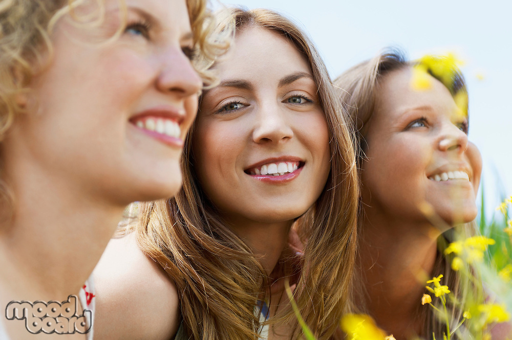 Young woman sitting with friends in flowery field portrait selective focus