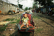Boy sit beside the railway at Tanah Abang district, Jakarta, indonesia. This area is one of the biggest slum area at Jakarta the Capital of Indonesia.