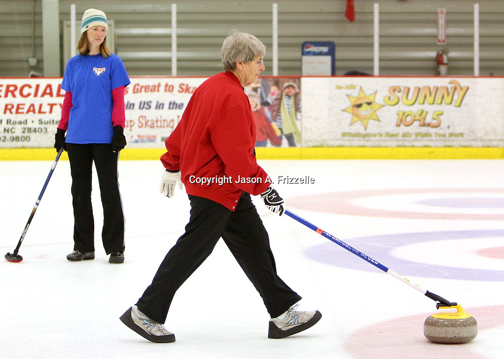 Maggie Schaber watches Peggy Hollen deliver a stone during a curling match at the Wilmington Ice House. (Jason A. Frizzelle)