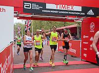 Jenson Button crosses the line #handinhand with Tom Dudden at the Virgin Money London Marathon, Sunday 26th April 2015.<br /> <br /> Scott Heavey for Virgin Money London Marathon<br /> <br /> For more information please contact Penny Dain at pennyd@london-marathon.co.uk