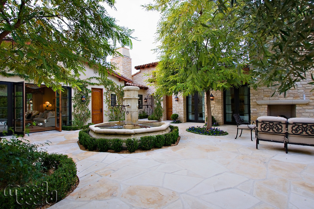 House exterior with a fountain  trees and patio furniture
