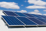 Solar electricity panels on corrugated tin roof under blue sky and cloud, providing green energy electric power.