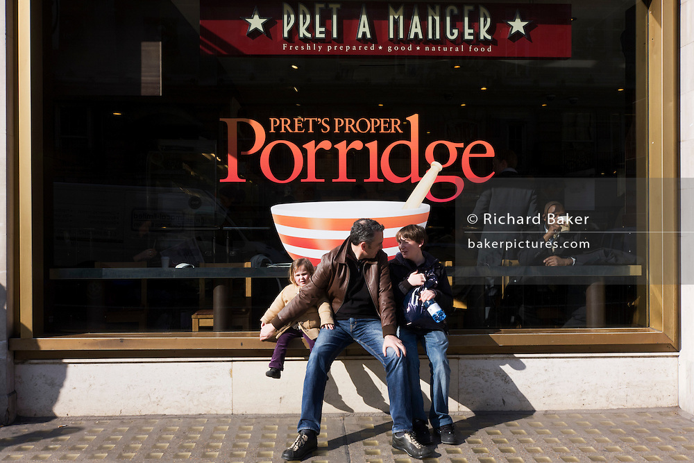 A father with his two children sits on a ledge outside a Pret a Manger lunchtime restaurant