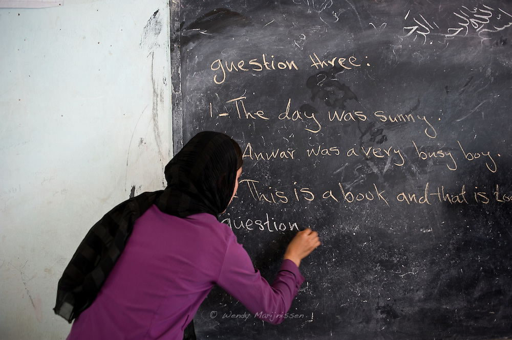 A teacher writes questions on the board for an English exam in a village in Badakshan. The area has some of the lowest literacy rates in the country.  School-age boys and girls attend irregular classes often held either in makeshift tents or in the open?when or if weather permits. Badakshan, Afghanistan, 2012