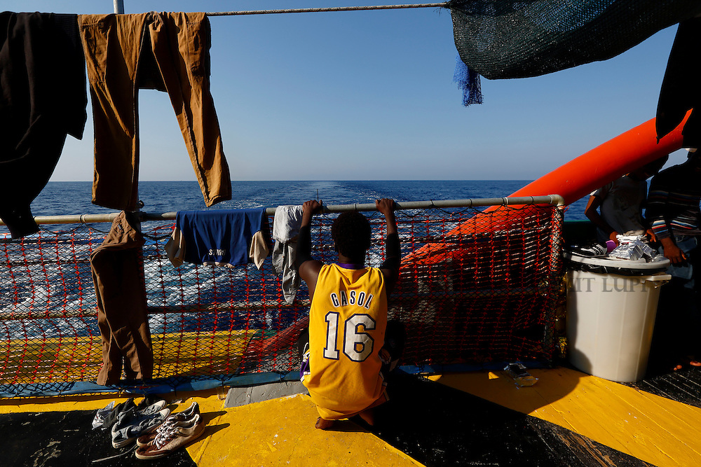 A migrant looks out to sea from the stern of the Medecins san Frontiere (MSF) rescue ship Bourbon Argos somewhere between Libya and Sicily August 8, 2015.  Some 241 mostly West African migrants on the ship are expected to arrive on the Italian island of Sicily on Sunday morning, according to MSF.<br /> REUTERS/Darrin Zammit Lupi <br /> MALTA OUT. NO COMMERCIAL OR EDITORIAL SALES IN MALTA
