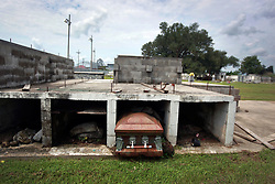 28 August 2014.  Merrick Cemetery, <br /> St Bernard Parish, Louisiana, USA. <br /> Hurricane Katrina 9 years later. <br /> A few miles south of the Orleans parish line, crumbling concrete tombs reveal their contents. Recovered remains were placed in new coffins FEMA paid to be reburied following their uprooting by Hurricane Katrina. Today the temporary tombs appear to have become the permanent resting place for many of the dead displaced by Hurricane Katrina. <br /> Photo; Charlie Varley/varleypix.com
