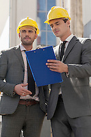 Young male engineers with clipboard discussing at construction site