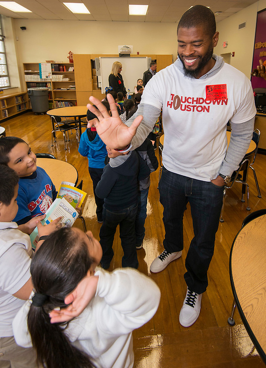 Wade Smith high-fives with students during a Touchdown Houston Read On literacy program at Ross Elementary School, December 2, 2016.