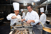 Chef Jerome Lacressonniere (R) and another unidentified chef work in the kitchen of Beige Alain Ducasse Tokyo in the Ginza district of Tokyo, Japan. Photographer: Robert Gilhooly..