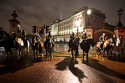 © Licensed to London News Pictures. 05/11/2015. London, UK. Mounted police on horses guard Buckingham Palace during An anti-capitalist  protest organised by the group Anonymous outside Parliament in Westminster on bonfire night 05, November 2015. Bonfire night, also known as Guy Fawkes night, is an annual commemoration of when Guy Fawkes, a member of the Gunpowder Plot, was arrested for attempting to blow up the House of Lords at parliament.   Photo credit: Ben Cawthra/LNP