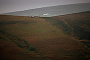 Single house in the distance over hillside in Dartmoor, Devon,  United Kingdom