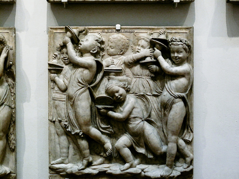 Across the room, a similar cantoria sculpted by Luca della Robbia, 1431,  is placed high on the wall.  But copies of the panels are hung below at eye level so that they are easier to examine.  Children and adolescents playing musical instruments, singing, and dancing.