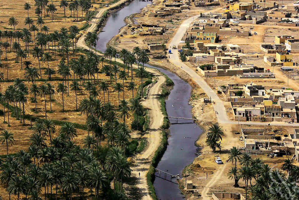 (Hold for story by Rich Oppel) Date palm orchards grow across a small river from an Iraqi village May 12, 2006 near the Iraqi city of Najaf. A U.S. sponsored program to help the Iraqi Agriculture Ministry spray orchards with insecticide aims to reverse the toll years of neglect and disease have taken on an industry that once was among Iraq's primary exports.