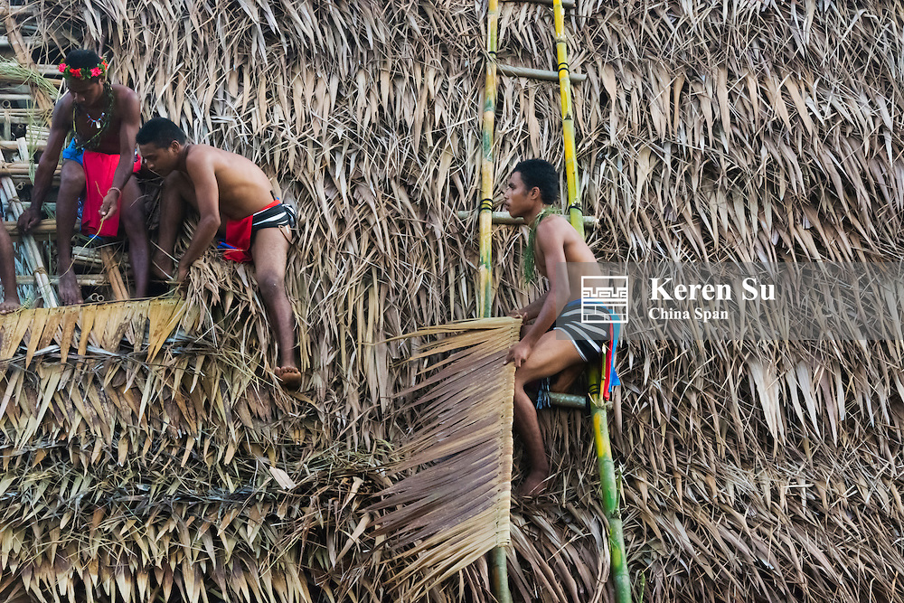 Yapese people putting on roof made of palm tree leaves, Yap Island, Federated States of Micronesia