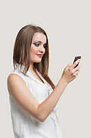 Beautiful young woman using cell phone against gray background