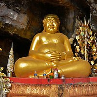 Gilded Happy Buddha on Mount Phousi in Luang Prabang, Laos  <br /> The Happy Buddha, known as Ho Tai, is usually depicted as shirtless, chubby, bald and with a big smile on his face or laughing.  According to legend, this monk allowed himself to get fat in order to ward off women and physical temptations.  In the Chinese culture he is popular among children for the gifts he bestows on them after they learn religious teachings.