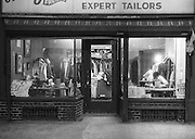 Tailor shop in Greenwich Village, New York City. Full view of shop with tailer at work on right. Full racks of clothing on three walls. Signs in windows for suede leather and chair caning. Tailor at table with sewing machine. Another table at left also has a sewing machine and other objects. Tall center table behind entrance door has a loose pile of clothing on top. Expert Tailors signage over windows. Night. Black and white.