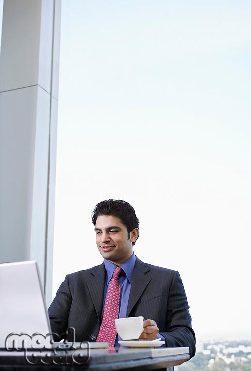 Business man using laptop holding tea cup