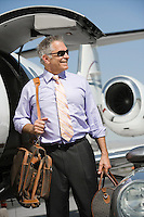 Senior businessman in front of private jet.