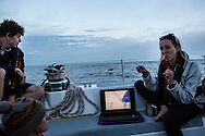 North Atlantic Ocean, September 2014.<br /> Marine biologist Stephanie Wright gives a lecture on microplastic on board the Sea Dragon while a dolphin jumping in the background distracts the audience! &copy; Chiara Marina Grioni