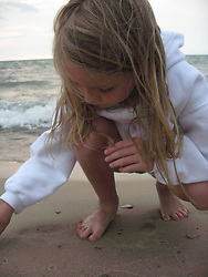Little girl playing in the sand near the waters edge