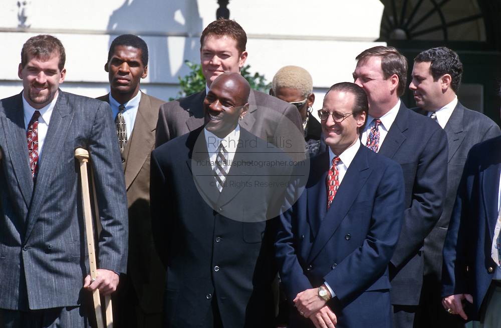 Chicago Bulls star Michael Jordan stands with Bulls Chairman Jerry Reinsdorf and teammate Bill Wennington during an event on the South Lawn of the White House April 3, 1997. The event honored the NBA Champion Chicago Bulls.