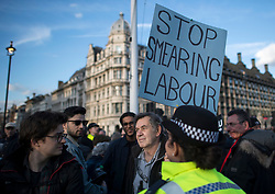 © Licensed to London News Pictures. 26/03/2018. London, UK. A supporter of Jeremy Corbyn holds a banner during a counter demonstration, as members of the Jewish community, Jewish leaders and supporters hold a demonstration outside the Houses of Parliament in London against Jeremy Corbyn, who they accuse of not acting on anti-semitic behaviour in the Labour Party. Photo credit: Ben Cawthra/LNP