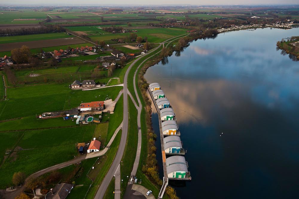 Nederland, Gelderland, Maasbommel, 15-11-2010. Recreatiegebied De Gouden Ham, onderdeel van rivier de Maas met drijvende woningen aan de Bovendijk. De recreatiewoningen maken onderdeel uit van een complex van buitendijks gebouwde tweede huizen, die (gaan) drijven bij hoog water. De woningen zijn bevestigd aan meerpalen om verschillen in waterhoogte op te vangen. .The Golden Ham recreation site, part of the river Meuse with floating houses on the Bovendijk (Upper Dike). The holiday homes are part of a  complex of houses build outside the dike that will rise and fall with the water level. The houses are attached to bollards to compensate water level fluctuations. .luchtfoto (toeslag), aerial photo (additional fee required).foto/photo Siebe Swart