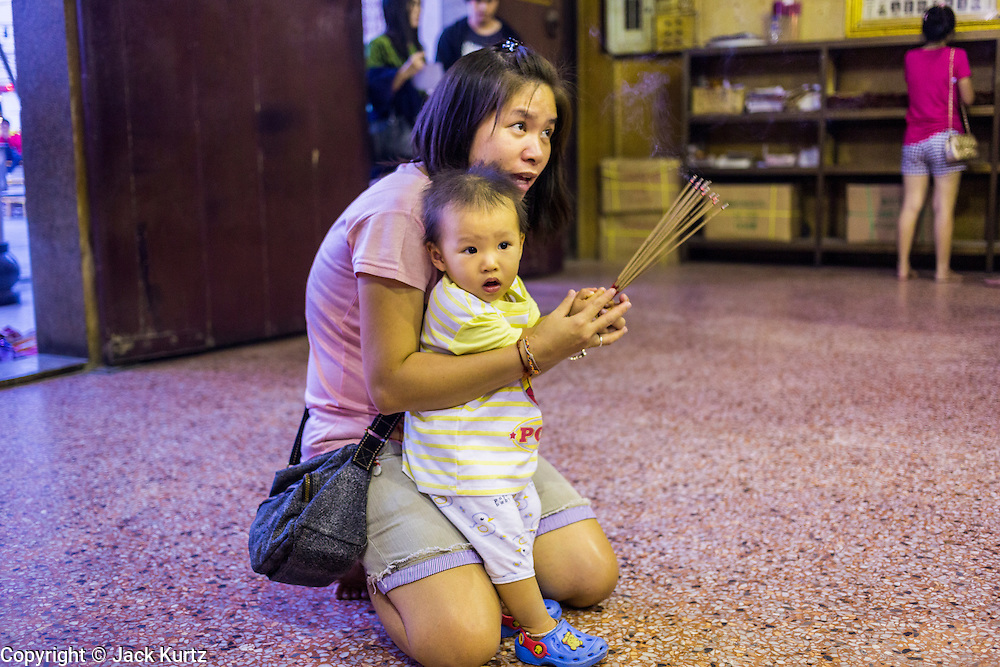 09 FEBRUARY 2014 - HAT YAI, SONGKHLA, THAILAND: A woman teaches her son to pray during Lunar New Year in the Tong Sia Siang Tueng temple in Hat Yai. Hat Yai was originally settled by Chinese immigrants and still has a large ethnic Chinese population. Chinese holidays, especially Lunar New Year (Tet) and the Vegetarian Festival are important citywide holidays.     PHOTO BY JACK KURTZ