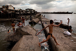 Children swimming and playing in the sea next to the slum area they live in. Used to the garbage it does not bother them.  Manila, Philippines