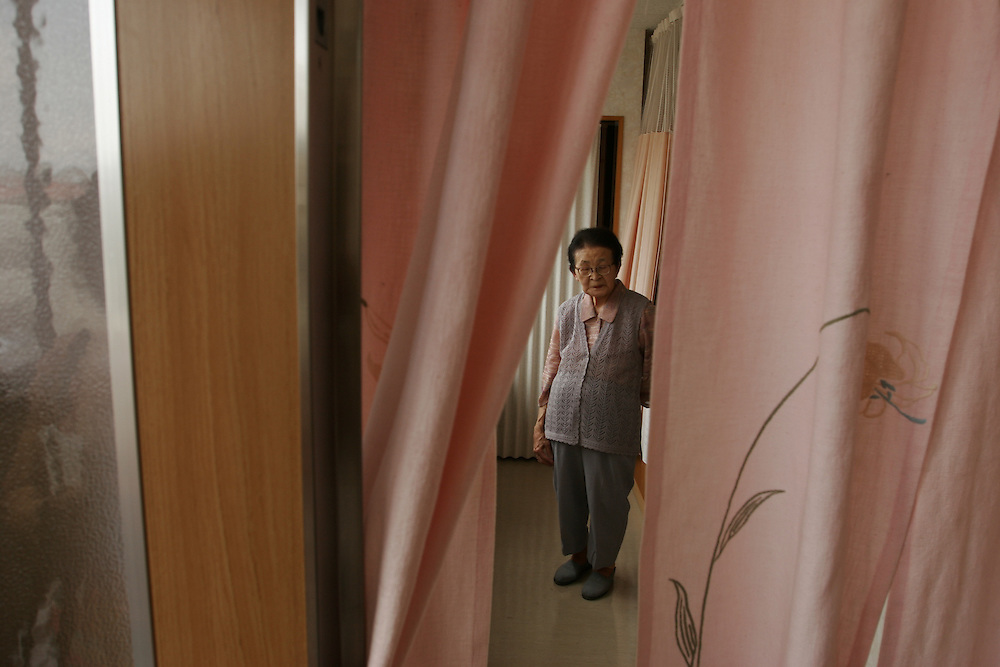"""Ms. Shizue Nobeta ( 86 years old ) In  her  Room at """"The   Grace Hill Nagasaki A Bomb Home""""Shizue Nobeta-86 ....Pink curtain lady....I was 1 km away from home on my way to work in a rice factory. ..My younger sister was working in a Castela factory near home. ..Mom was working in a department store and dad was off from work and was saved before he was near his home shelter. .. I was waking to work with 4 or 5 people and we were thrown far away after the explosion . after the explosion I decided to go home and everything was dark ..After the explosion I saw 20 bodies lying on the ground , I heard about it from Hiroshima but I couldn't believe this was the same thing..Next morning everyone was told to go to the shelter and as I looked back I saw Nagasaki was a red sea of fire ..After a few days in the shelter I should get back to work , on my way back to work I saw kids lying on the futon as if they were sleeping but they were dead ..Everyone was injured so there was no to help ..I saw this small child crying  momy momy , his grandparents holding him. Even today I hear  his cries calling for his momy . ..The smell of dead bodies , a man whose skin was embedded with glass..It was a like a dead city , silent , the only sounds were the screams of the injured...All my family got sick with diarrhea for one month. There was no medicines, but my mom gave us umeboshi , I think that help a lot. Everything is lost on war, you are naked...."""