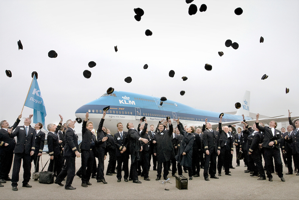 Netherlands. Schiphol-Oost, 03-12-2003. Photo: Patrick Post. KLM Jumbo looses Flight Engineer. About 80 KLM Flight Engineers in uniform give a salute, by throwing their hat in the sky. During 75 years the flight engineer brought useful information in the evolution of modern aircraft operations. Despite, the evolution in the technical environment enforced the modern aircraft to fly without an engineer. The KL875 ( 747-300 ) to New Delhi and back to Amsterdam was the last  engineered flight of the classic Jumbo within KLM.