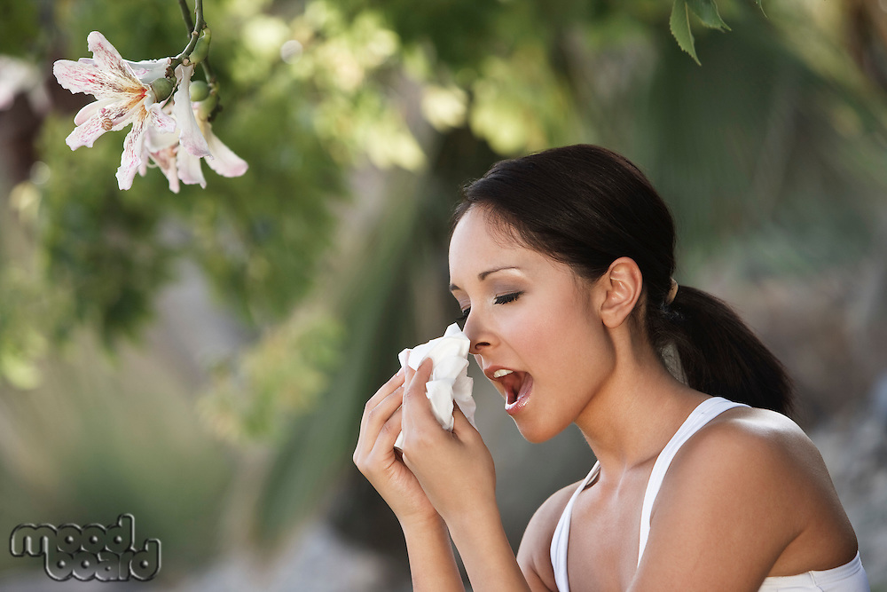 Woman sneezing under tree