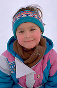 Girl age 4 dressed in snow suit ready for sledding with family.  St Paul  Minnesota USA