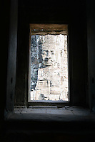 Stone Face Sculpture Seen Through Window of Ruins