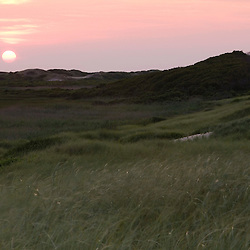 The sun sets behind the dunes at Head of the Meadow Beach on the Cape Cod National Seashore in Truro, Massachusetts.