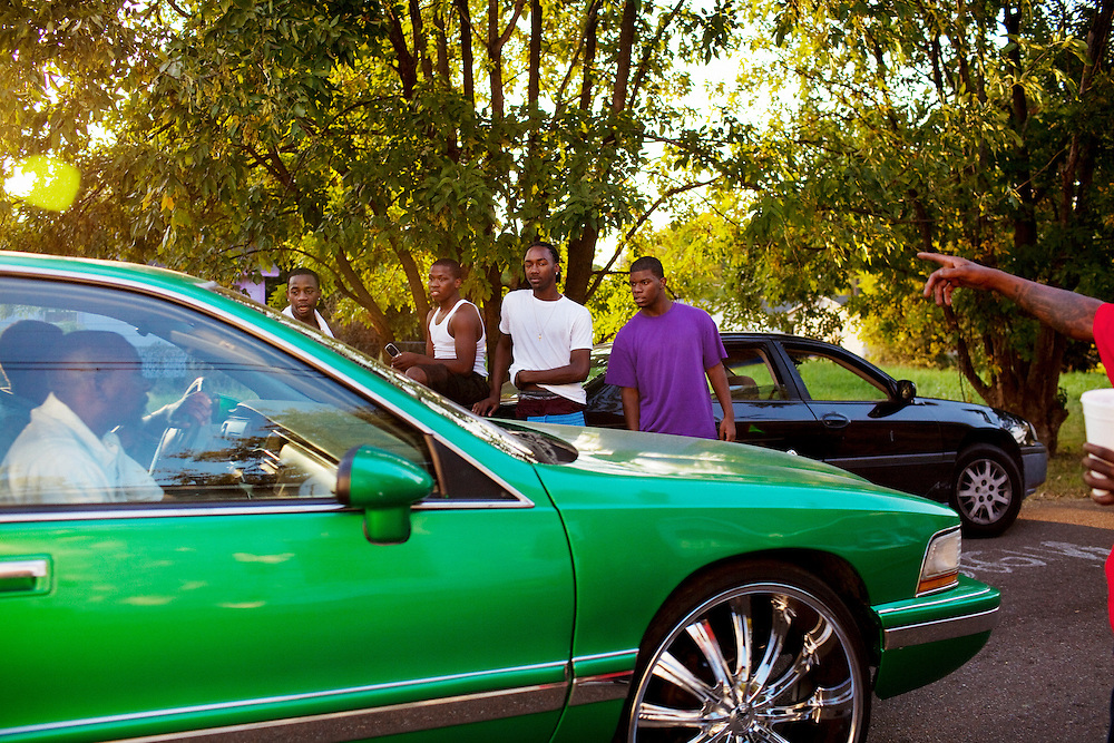 Young men loiter about as a pimped out ride rolls by in the Baptist Town neighborhood of Greenwood, Mississippi on Friday, September 24, 2010