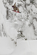 Japanese professional snowboarder Kazu Kokubo does a tail grab off a pillow gap in the woods of the Sproatt snowmobile zone just south of Whistler, British Columbia