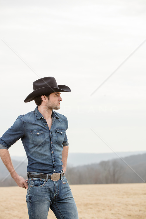 cowboy looking out on a hilly field outdoors