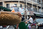 A woman is carrying a bamboo tray filled with food on a city street in Phnom Penh, Cambodia.
